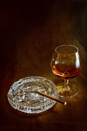 a glass of brandy and a crystal ashtray with a cigarette in the background of brown suede