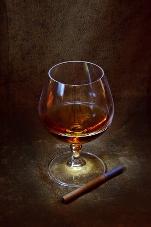 a glass of brandy and a cigarette in the background of brown suede Stock Photo