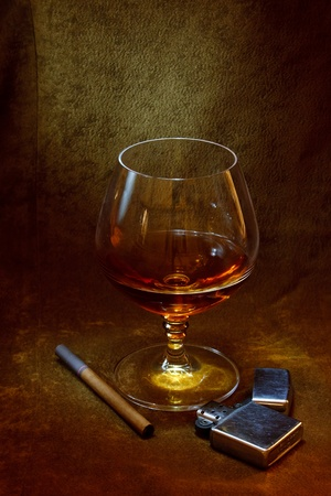 a glass of cognac, a cigarette lighter and on the background of brown suede