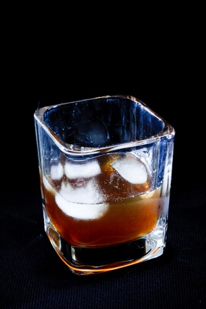 intoxicate: stylish glass of whiskey on the rocks on a black background