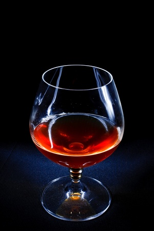elegant glass of brandy on a black background