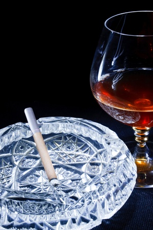 a glass of brandy and a cigarette in an ashtray on a black background Stock Photo