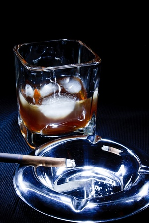 a glass of brandy and a cigarette in an ashtray on a black background photo