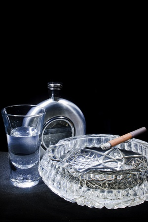 cigarette in the ashtray, glass, flask on a black background