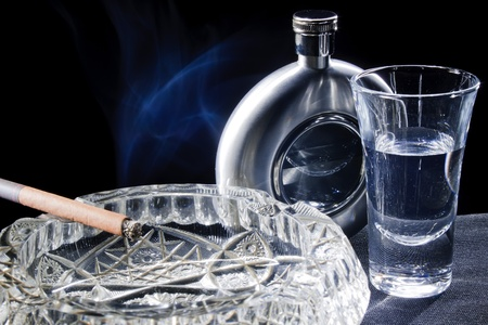 cigarette in the ashtray, glass, flask on a black background photo