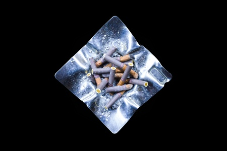 Decorated silver ashtray with cigarette butts isolated on black background photo