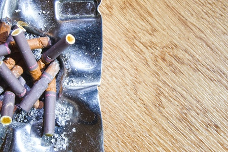 frowzy: Decorated silver ashtray with cigarette butts over wooden table Stock Photo