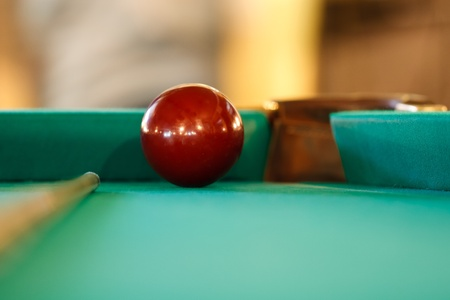 red cue ball at the pocket and the cue for Russian billiards Stock Photo