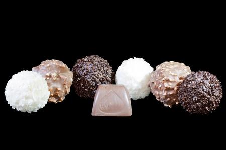 luxury chocolates in white, black and milk chocolate, isolated on black background photo