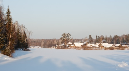 view of the winter village on the shore of the pond Stock Photo