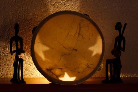 촛불의 부드러운 빛에 두 아프리카 인형, 탬버린 스톡 사진