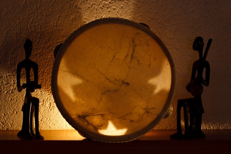 two African figurines and tambourine in the soft light of candles
