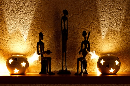 three African figurines and tambourine in the soft light of candles