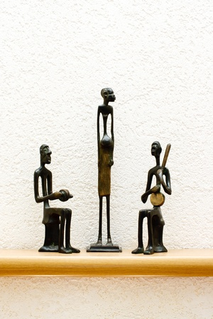 wood figurine: three African statues against the wall