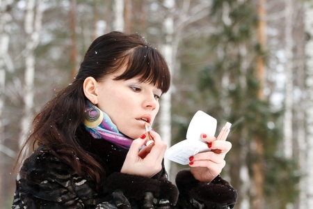 non urban 1: portrait of a beautiful young girl with cosmetics on background of a winter forest