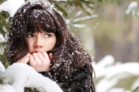 겨울 숲의 배경에 젊은 여자의 근접 촬영 초상화