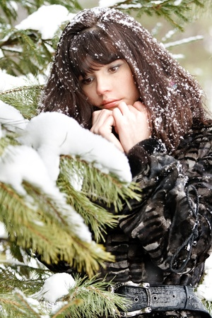 portrait of a young girl with the snow in her hair against the winter forest Stock Photo