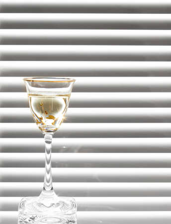 a glass of liquor on the black and white background photo