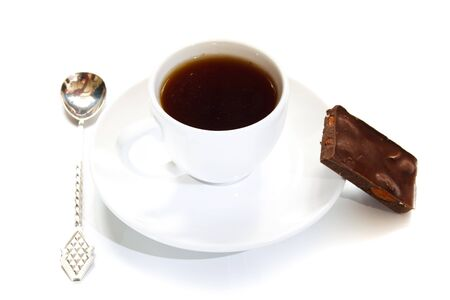 cup of coffee with a spoon and a piece of chocolate on a white background