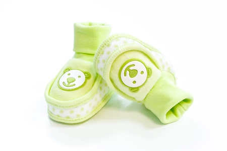 green baby booties with dots on a white background Stock Photo