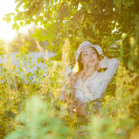young girl in a white shirt and hat, in the sunset Stock Photo