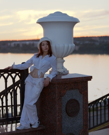 young girl in a white shirt and hat, in the sunset at the lake