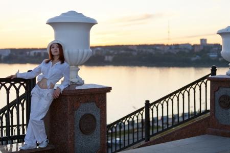 호수에서 일몰에 흰색 셔츠와 모자에 젊은 여자,
