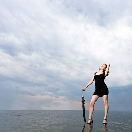 Girl with umbrella stands on the surface of the water against the backdrop of a stormy sky
