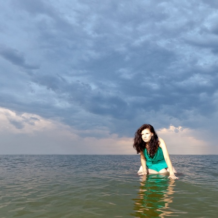 girl sitting on the surface of the water against the backdrop of a stormy sky photo