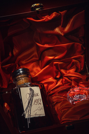 Luxurious bottle of Armagnac in a box made of mahogany red material