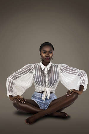 A studio portrait of a serene young black female sitting on the floor with short black hair and pink nails wearing a white sheer blouse with denim shorts and silver jewelry.