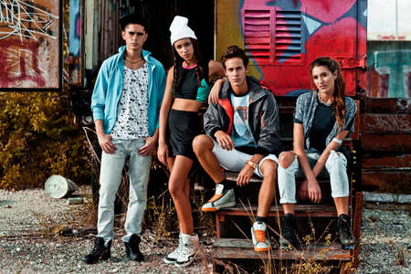 Portrait of an interracial group of 4 young adults hanging out on wooden steps in front of an open graffiti sprayed container on a vacant lot during a warm summer day wearing cool urban outfits.