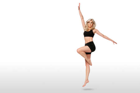 Portrait of a dancing fit young white female athlete with curly long blond hair posing by herself in a studio with a white background wearing black shorts & sports bra.