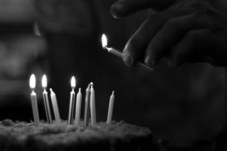 Man Lighting Candles on a Birthday Cake in Black and White Zdjęcie Seryjne