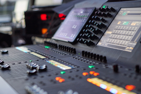 side view on mixing console in use with many lights during event