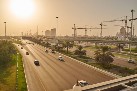 afternoon sun shining on Abu Dhabi street with grand mosque in back