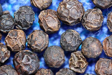 Closeup of peppercorns on a textured blue background
