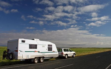 Offroad caravan and 4WD on tour in the  Australian outback against a brilliant green grassy plain and blue sky with interesting clouds