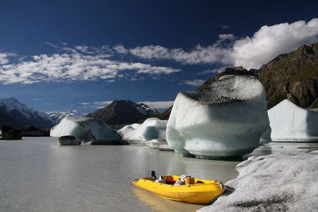Huge sculptured icebergs floating in a glacial lake with ice covered mountains in background against a dramatic blue sky.