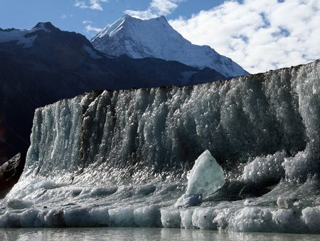 Massive ice wall on floating Iceberg on the Tasman Glacier Lake with snow covered Mount Cook in the bckground