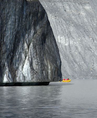 The toe or snout of a large glacier taken from a boat on the glacial lake at the glaciers foot.