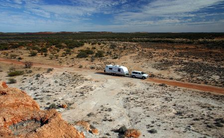 Offroad caravan and four wheel drive on dirt track in stunning outback scenery with blue partly cloudy skies.