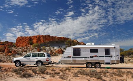 Four wheel drive and offroad caravan in outback Australia against a stunning red rock outcrop with an deep blue sky and interesting cloud formations Stock Photo