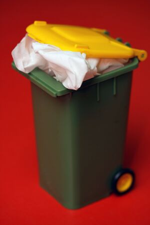 Mini re-cycling rubbish bin overflowing with a white tissue on a highly contrasting red background