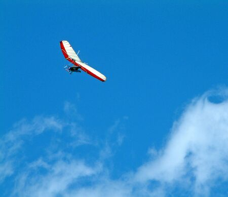 Hang glider on a clear blue sky with cloud wisps