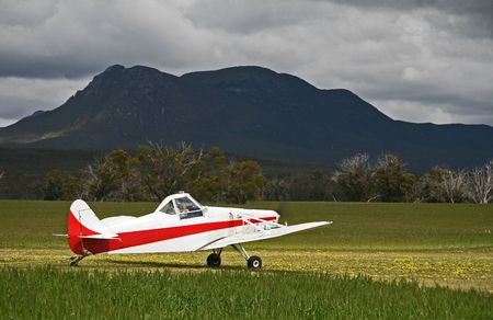 White and red glider tow plane spotlighted by sun in bright green wheat field, with a contrasting moody back drop of a mountain and foreboding sky.  Stock Photo