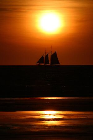 A yatch under full sail diectly under setting sun in a bright orange background and horizon with reflections of the sun in the sand in the foreground. Stock Photo