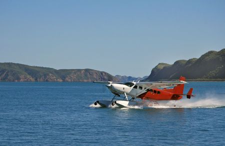 Landscape view of purple and white Cessna Caravan floatplane commencing take off on calm waters with a mountain range background