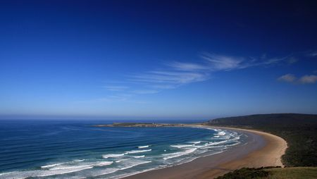 Landscape view of a deserted beach with rows of white breakers and a brilliant clear blue sky with an odd white cloud wisp