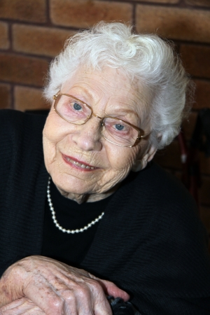 Portrait shot of a smiling old lady with wrinkled face and pure white hair with her hands crossed in a pensive gesture